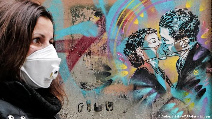 A work of graffiti depicts a couple kissing while wearing masks.