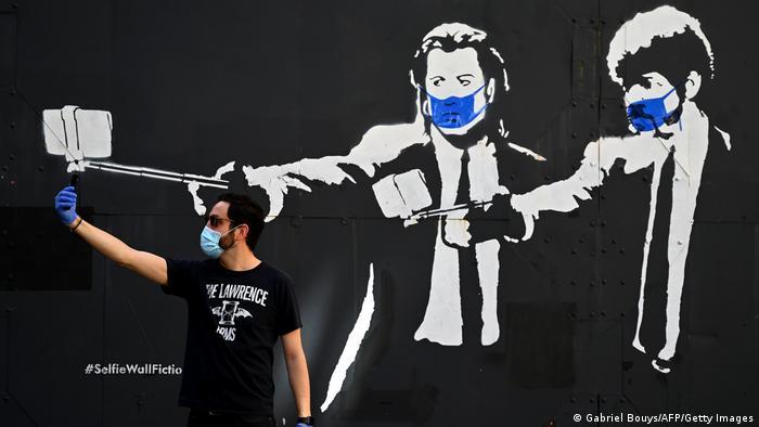 John Travolta y Samuel L. Jackson en la clásica imágen de Pulp Fiction, sujetándo un palo de selfie en vez de un arma de fuego.