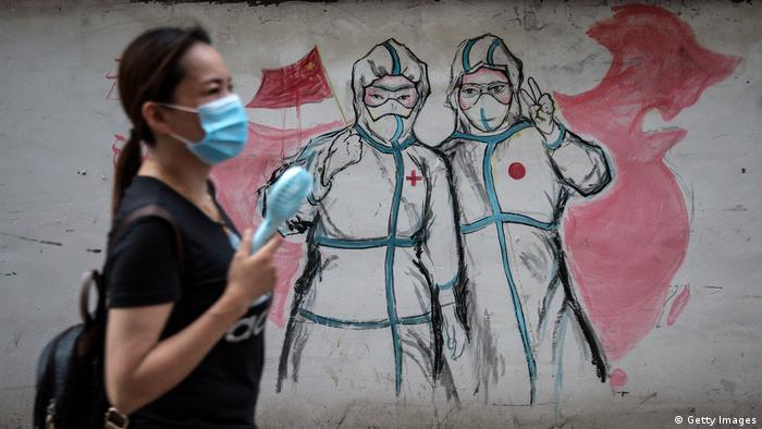 A woman walks by a graffiti painting on the wall depicting two nurses; one holding a Chinese flag and the other making a peace sign.