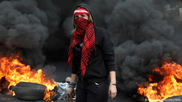 demonstrator stands near a burning fire blocking a road, during a protest against the fall in Lebanese pound currency and mounting economic hardships, in Zouk, Lebanon