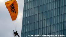 An activist of environmental organization Greenpeace flies with a motorized paraglider past the European Central Bank in Frankfurt, Germany, Wednesday, March 10, 2021. Two activists landed on the roof of a side building and unrolled a banner to protest against the ECB's climate policy. (AP Photo/Michael Probst)