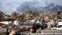 """*** Dieses Bild ist fertig zugeschnitten als Social Media Snack (für Facebook, Twitter, Instagram) im Tableau zu finden: Fach """"Images"""" —> Weltspiegel/Bilder des Tages *** ***Archibild*** epa02634263 As Japan prepares for a potentially massive nuclear contamination a solitary tsunami survivor weeps in tears amid debris in the devastated town of Natori, Miyagi prefecture, Japan, 14 March 2011. Radiation levels at a damaged nuclear power plant at Fukushima, 240 kilometres north of Tokyo, were rising well above the legal limits, top government spokesman Yukio Edano said. Reactors at the Fukushima I and II plants lost their cooling functions after power and backup generators were cut off by the quake on 11 March 2011. EPA/STRINGER JAPAN OUT MANDATORY CREDIT EPA/ASAHI SHIMBUN MANDATORY CREDIT: EPA/ASAHI SHIMBUN ++"""