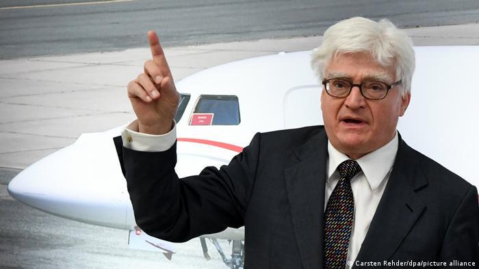 Winfried Stöcker Mediziner und Unternehmer sowie Inhaber des Flughafens Lübeck, spricht nach der Übergabe der Flughafenlizenz der Europäischen Agentur für Luftsicherheit (EASA). Im Hintergrund ein Flugzeug.