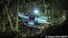 This picture taken on March 10, 2021 shows rescuers evacuating victims of a bus accident that plunged into a ravine in Wado subdistrict, in Sumedang, West Java, which claimed 27 lives. (Photo by BAGUS AHMAD / AFP)