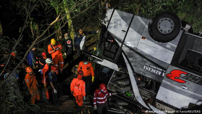 Rescue workers standing next to an upturned bus