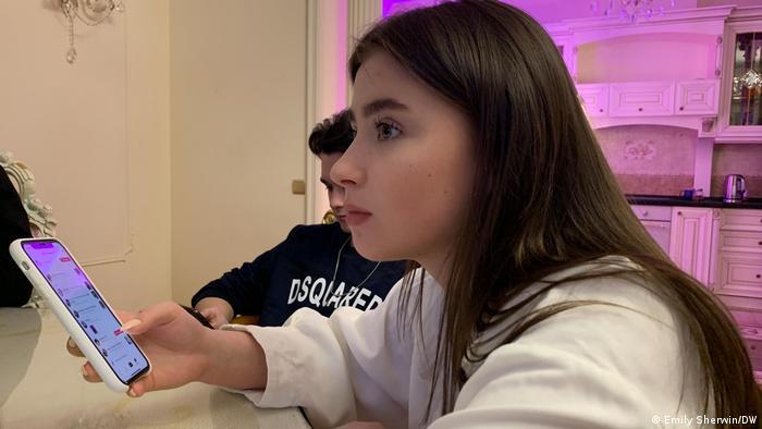 TikToker Veronika Reznikova checking her feed on TikTok (Emily Sherwin/DW)