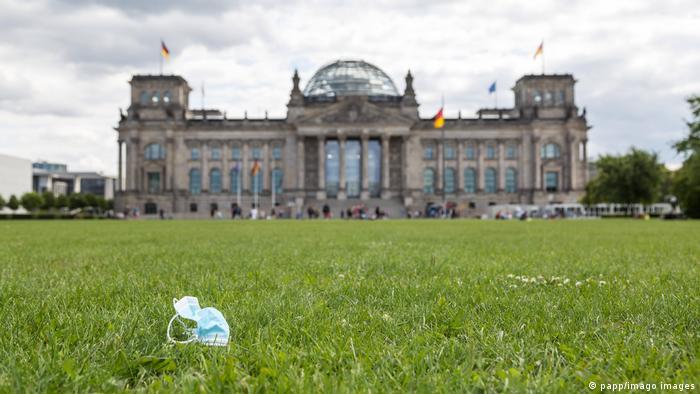 Маска на фоне здания, в котором заседает бундестаг