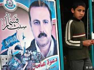 A Palestinian youth walks out of a store covered with posters of of assassinated Mahmoud al-Mabhouh