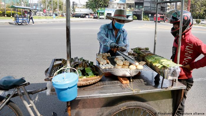 A vendor sells grilled banana and potatoes on a street in Phnom Penh