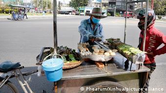 Уличный торговец в медицинской маске в столице Камбоджи Пномпене
