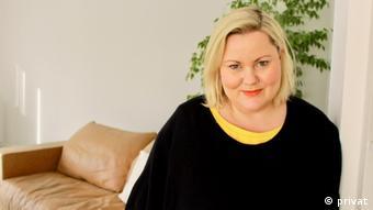 Psychologin Ulrike Bossmann steht vor einer Couch und einrr Pflanze
