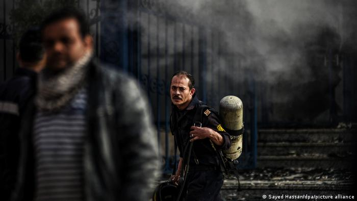 An Egyptian firefighter works to put out a blaze at a factory north of Cairo