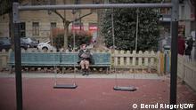 Italien Geburten Corona. Ältere Dame in Mailand sitzt hinter leerer Schaukel auf Kinderspielplatz. Symbolbild für schwindene Kinderzahl in Corona-Pandemie. Aufgenommen am 10.03.2021. Foto: Bernd Riegert, DW, alle Rechte