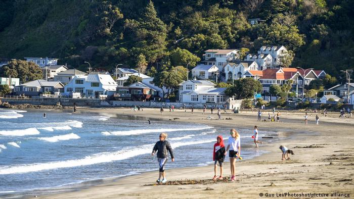 Pessoas caminham em praia na Nova Zelândia