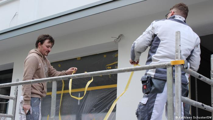 Two handymen tear off masking tape from the facade of a building