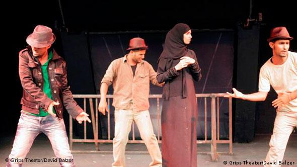 Three male actors surround the young female protagonist on stage