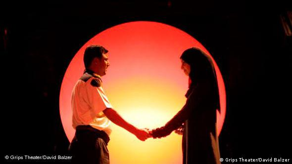 A couple holds hands in front of a sun prop at the end of the play