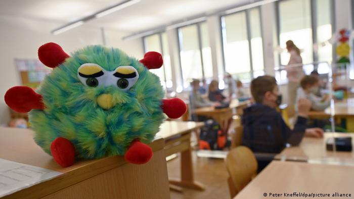 Kinder sitzen während des Unterrichts in einer Grundschulklasse mit Plexiglas-Trennscheiben zwischen den Plätzen an ihren Tischen. Im Vordergrund steht ein Plüschtier mit Mund-Nase-Schutzmaske.