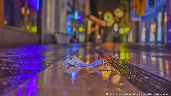 Eine Straße fotografiert von unten in der Dämmerung bei Regenwetter, rundum Lichter von Leuchtreklamen, auf dem Boden liegt eine Maske