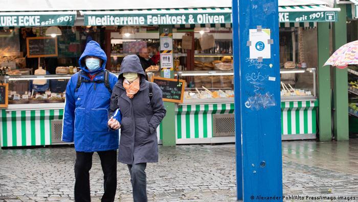 Two people wears face masks and raincoats at an outdoor market