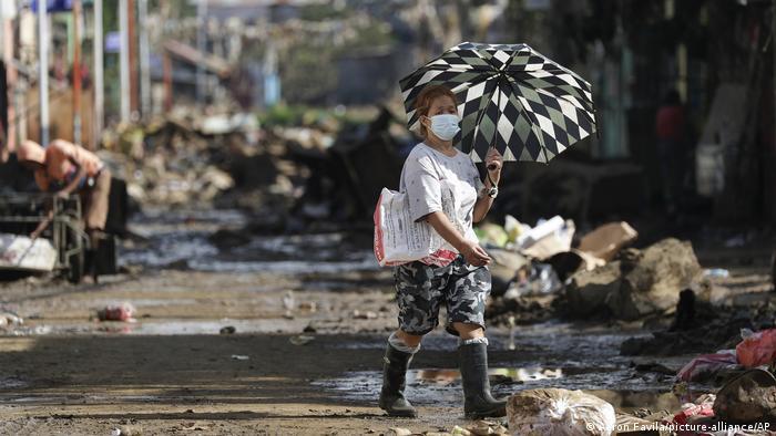 Eine Frau auf den Philippinen geht nach dem abgeklungenen Taifun Vamco über eine Straße voller Schlamm