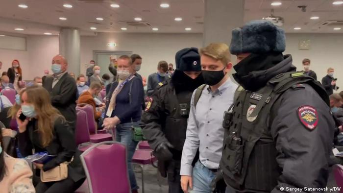 Двое полицейских уводят из зала участника форума Муниципальная Россия