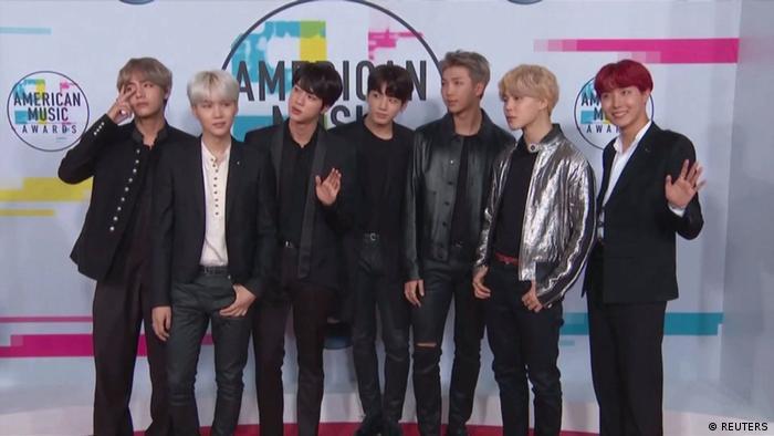 K-Pop-Band BTS posiert mit sieben Bandmitgliedern auf einer Bühne und winkt in die Kamera.