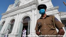 A police officer stands guard in front of St. Anthony Church in Colombo, Sri Lanka on the anniversary of the 2019 Easter bombings