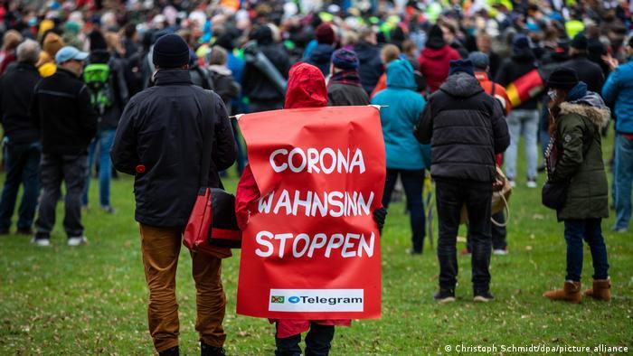 Eine Person trägt auf einer Demonstration ein Plakat auf dem Rücken, mit der Aufschrift Corona-Wahnsinn stoppen.