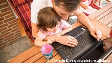 ILLUSTRATION - Ein Mann sitzt am 17.07.2020 in Weyhe mit seiner Tochter auf einer Terrasse und arbeitet an einem Laptop (gestellte Szene). Foto: Christin Klose
