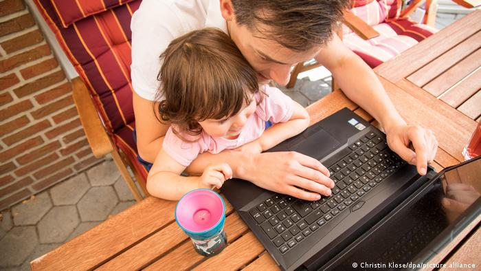 A father and his young daughter check his laptop at home