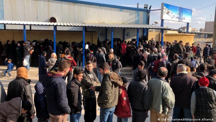 Syrians queue in Aleppo in February 2021 to buy bread