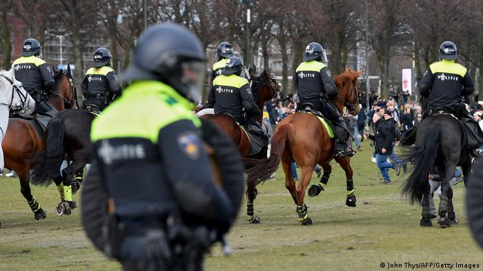 Dutch anti-riot police and mounted police officers detain confront a demonstration against the government and anti-COVID measures at The Hague