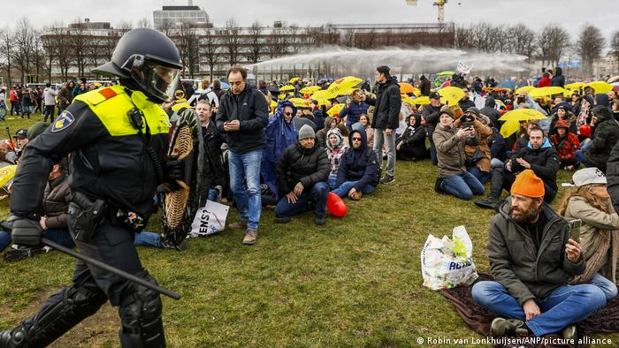 Protesters sit on the ground at a field in The Hague as authorities approach
