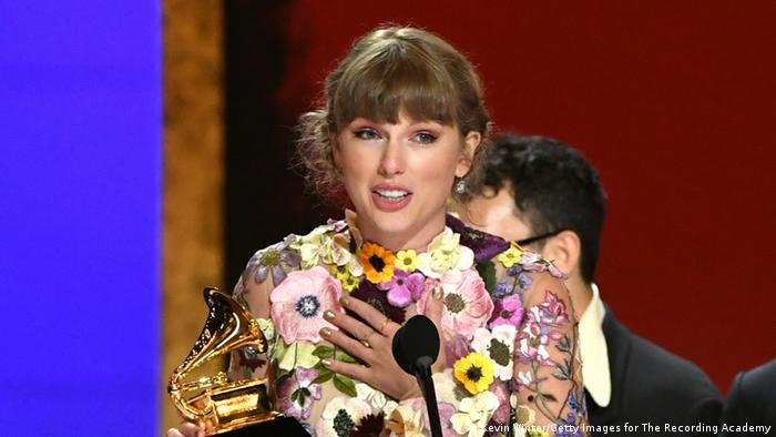Taylor Swift accepts her Grammy trophy for best album onstage