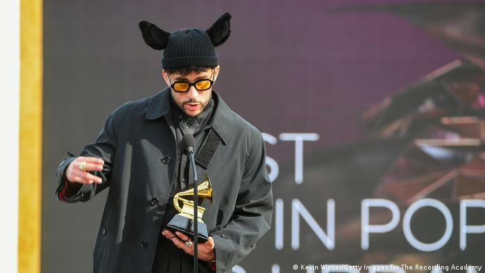 Bad Bunny accepts his Grammy trophy while wearing a hat with ears