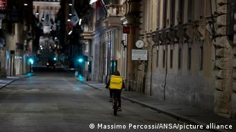 Доставщик продуктов на велосипеде на пустынной из-за локдауна улице Рима