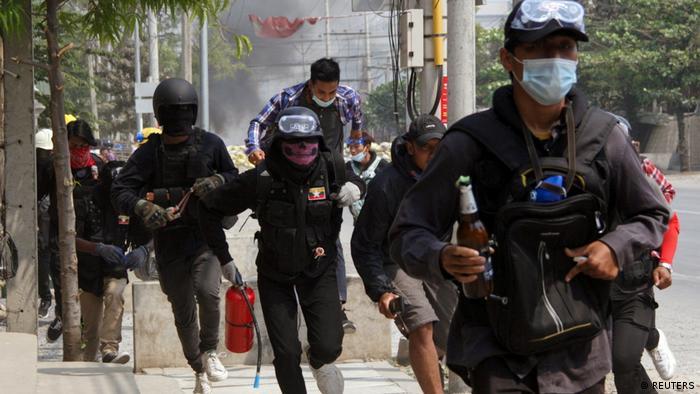 Des manifestants courent près d'une barricade lors d'une manifestation anti-coup d'État à Mandalay