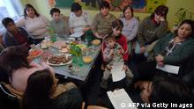 Ostrava, CZECH REPUBLIC: Kumar Vishwanathan (R-lower corner), volunteer for Roma people and for Roma integration into Czech society, debates with 12 of the 87 gypsies who have lodged complaints against their alleged forced sterilisation in local hospitals over the last 40 years, 03 February 2006, in the community center in the eastern city of Ostrava. Discounted by Czech authorities as a ''myth'' for many years, a Czech court recently upheld one of the complaints saying that the women's human rights had been infringed upon. AFP PHOTO / MICHAL CIZEK TO GO WITH AFP STORY (Photo credit should read MICHAL CIZEK/AFP via Getty Images)