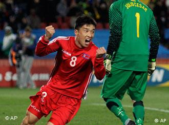 North Korea's Ji Yum Nam, left, celebrates after scoring a goal against Brazil goalkeeper Julio Cesar, right, during the World Cup group G soccer match between Brazil and North Korea
