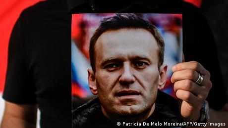 Portrait of Alexei Navalny held by demonstrator in Lisbon