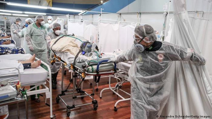 Profissionais de saúde empurram maca dentro de hospital de campanha na Grande São Paulo