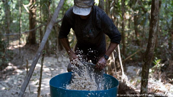A gold miner washes a carpet used to trap gold fragments as he works at an illegal mine in the Amazon jungle, in the Itaituba area of Para state, Brazil