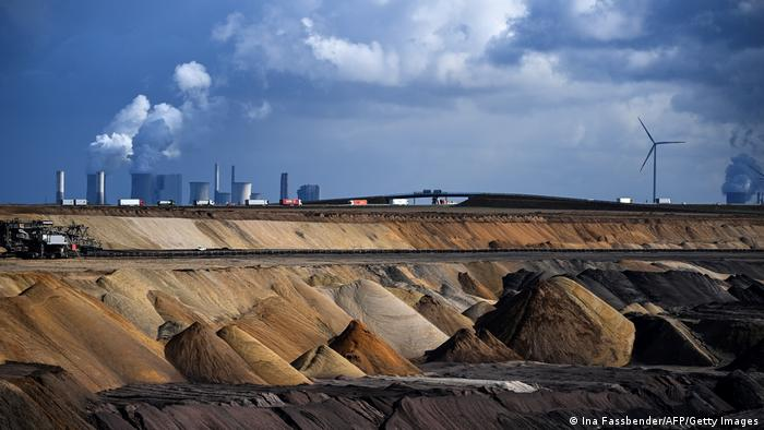 A German coal mine with a wind turbine and a coal plant in the background
