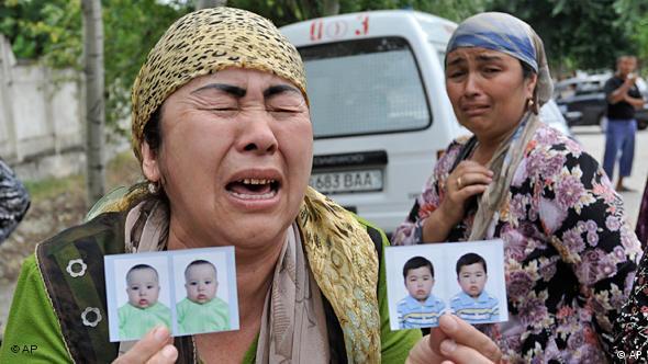 Eine verzweifelte Flüchtlingsfrau hält die Passfotos von zwei vermissten Kindern in die Kamera (Foto: AP)