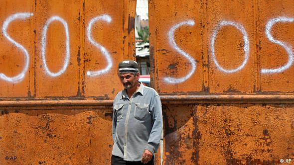 An Uzbek men walks with a sign SOS on gates in suburb of the southern Kyrgyz city of Osh