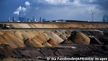 Coal plants near wind turbines behind an open-cast coal mine in Germany