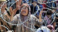***File***Uzbek woman Matluba, centre, who says she fled from the southern Kyrgyz city of Osh after her family were killed, weeps as she stands in line in no-man's-land near the Uzbek village of Jalal-Kuduk waiting for permission to cross into Uzbekistan, Monday, June 14, 2010. Many thousands of refugees fled a pogrom that began last week in southern Kyrgyzstan. (AP Photo/Anvar Ilyasov) Die Bundesregierung hat in der Nacht zum Dienstag, 15. Juni 2010, die Evakuierung von 89 Auslaendern aus dem vom Buergerkrieg erschuetterten suedkirgisischen Osch ermoeglicht. Das berichtete Aussenminister Guido Westerwelle in Berlin. (AP Photo/Faruk Akkan,CHA)