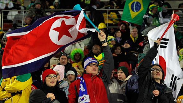 Fans waving both a South Korean, right, and a North Korean flag, left, at the match between North Korea and Brazil