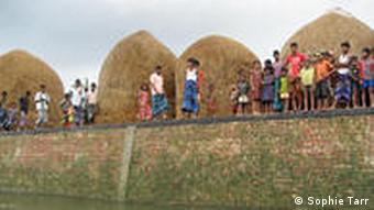 The people of Nawabpur have built a wall to keep rising floodwaters at bay